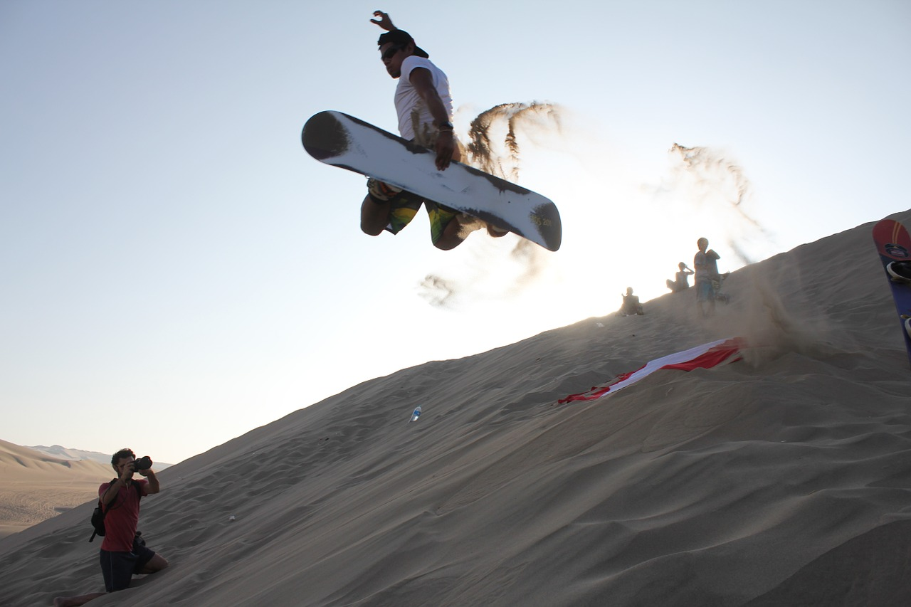 A man sandboarding while others are taking pictures.